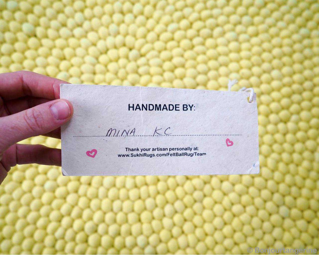 girls hand holding a card yellow felt ball contemporary rugs