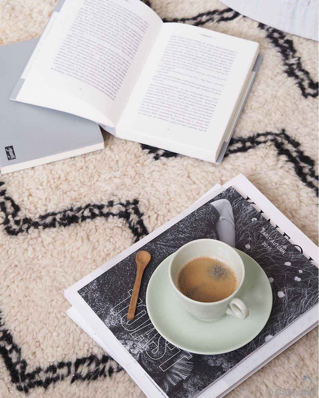 hand knotted books and cup of tea on magazine oriental rugs