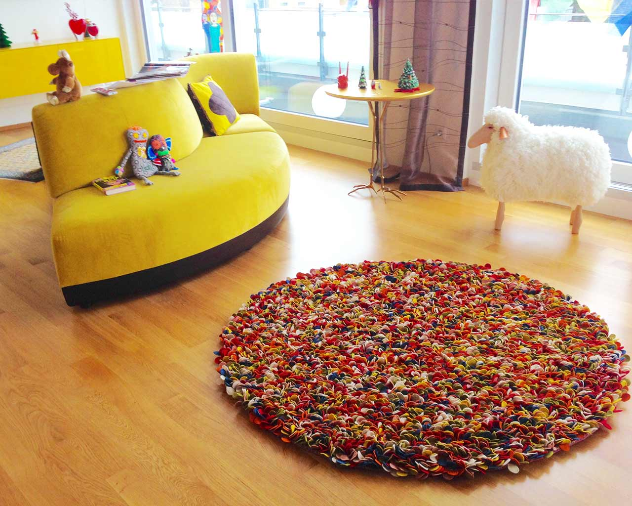 multi colour wool felted rugs yellow sofa wooden flooring white sheep